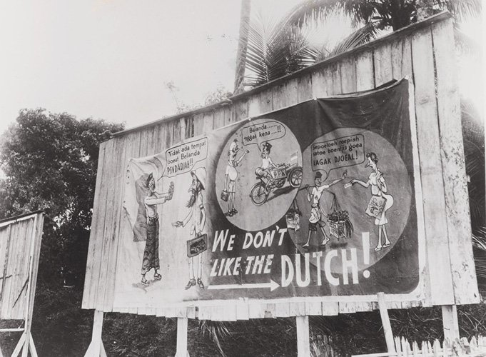 Foto 1 Straatbeeld met een paneel met anti-Nederlandse propaganda We don't like the Dutch. 1945  (Bron Beeldbank NIMH)