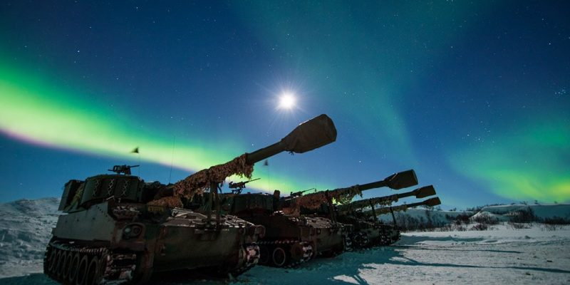 """""""Norwegian artillery under the northern lights. Modern CF operations face a closely tied to-step dilemma for force-commanders: when to initiate active sensors and when to engage."""" Photo: Forsvaret, Ole-Sverre Haugli"""