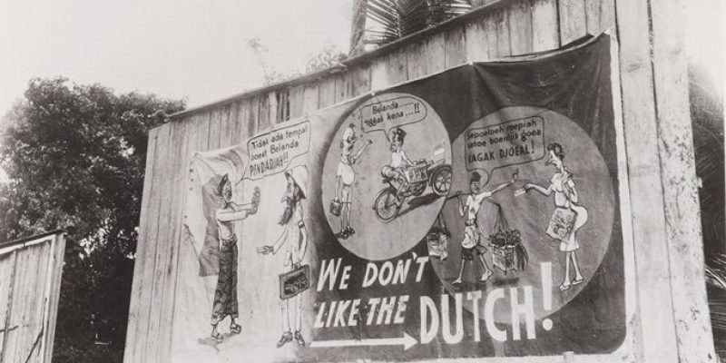 Foto 1 Straatbeeld met een paneel met anti-Nederlandse propaganda We don't like the Dutch. 1945  (Bron Beeldbank NIMH)